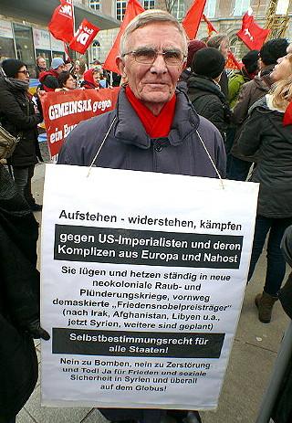 Demonstrant mit umgehängtem Schild: »Aufstehen - widerstehen, kämpfen gegen US-Imperialisten und deren Komplizen aus Europa und Nahost…«.